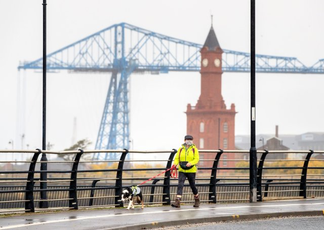 A woman wearing a face mask walks by the Tees Transporter Bridge in Middlesbrough.