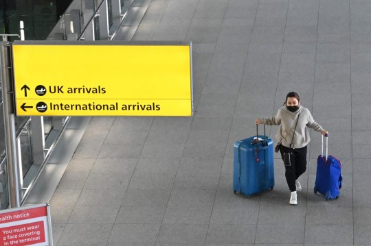 A passenger with luggage is seen at London Heathrow Airport in west London on February 14, 2021 .