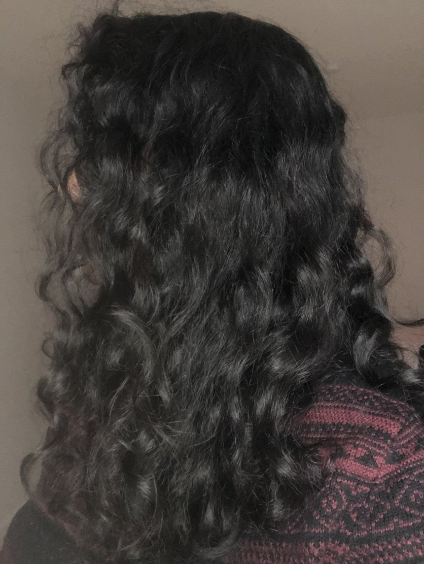 Woman's curly hair shown from the side
