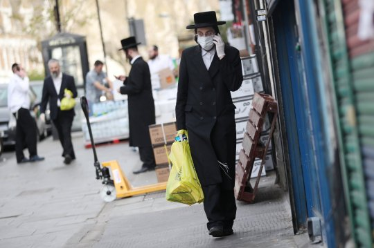 An Orthodox Jewish man wearing a protective face mask and gloves is seen in Stamford Hill, as the spread of the coronavirus disease (COVID-19) continues, London, Britain, April 8, 2020. REUTERS/Hannah McKay - RC2F0G9SSW0H