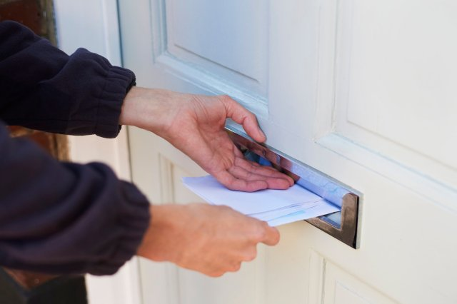 Close up of postman delivering post through resident's letterbox. Frome Neighbourhood Policing Team is looking for a man who has been pushing cash and letters through random residents' postboxes.