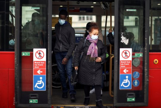 People wearing protective masks get out of a bus amid the coronavirus disease (COVID-19) outbreak, in London, Britain February 22, 2021. REUTERS/Hannah McKay