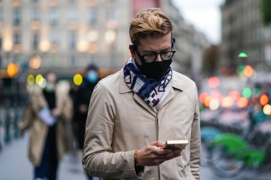 PARIS, FRANCE - OCTOBER 02: A guest wears, glasses, a face mask, a scarf, a beige trench coat, outside Yohji Yamamoto, during Paris Fashion Week - Womenswear Spring Summer 2021, on October 02, 2020 in Paris, France. (Photo by Edward Berthelot/Getty Images)