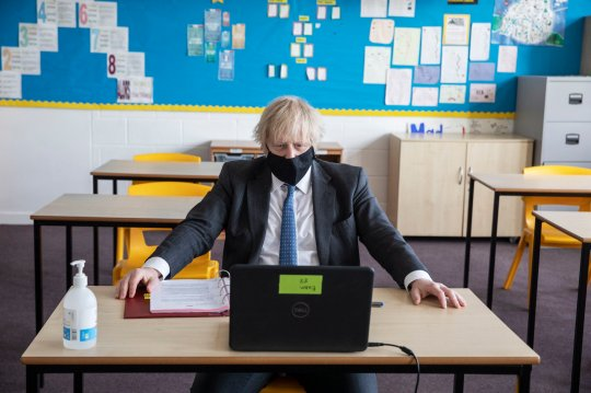 Britain's Prime Minister Boris Johnson takes part in an online class, during a visit to Sedgehill School in Lewisham, south east London, Tuesday, Feb. 23, 2021, to see preparations for students returning to school. Johnson has announced a gradual easing of one of Europe???s strictest lockdowns on, saying children will return to class and people will be able to meet a friend for coffee in a park in two weeks??? time. But people longing for a haircut, a restaurant meal or a pint in a pub have almost two months to wait, and people won???t be able to hug loved ones that they don???t live with until May at the earliest. (Jack Hill/Pool Photo via AP)