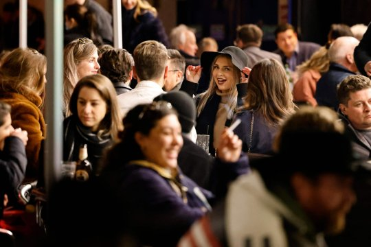 Customers enjoy drinks at tables outside the pubs and bars in the Soho area of London, on April 12, 2021