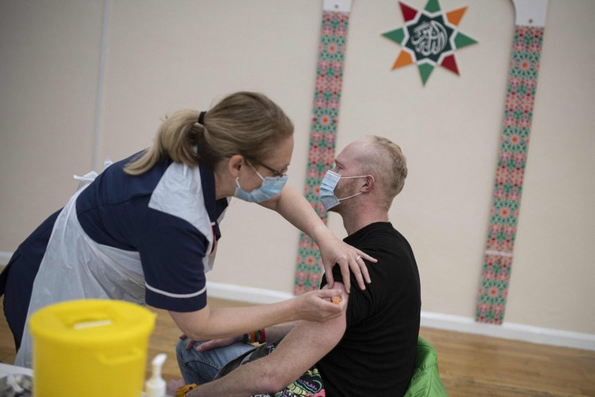 A health worker administers a dose of the AstraZeneca/Oxford Covid-19 vaccine to a patient at a vaccination centre set up at the Karimia Institute Islamic centre and Mosque in Nottingham, central England on April 6, 2021. (Photo by OLI SCARFF / AFP) (Photo by OLI SCARFF/AFP via Getty Images)