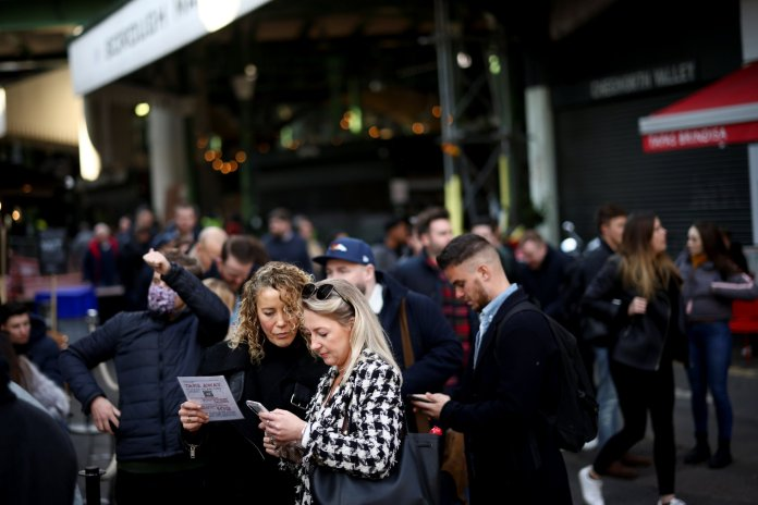 People browse the menu while queuing outside a pub