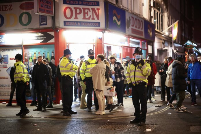 Police patrol as people party in Soho