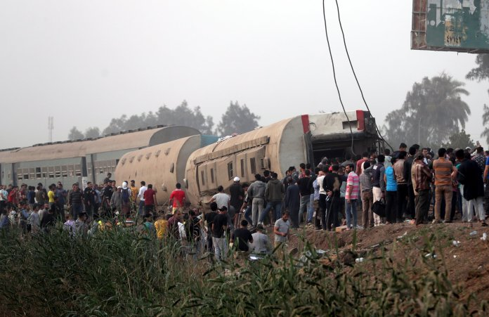 epa09143789 People stand near the damaged cars of a derailed passenger train in Toukh, Al Qalyubia Governorate, north of Cairo, Egypt on April 18, 2021. According to the Ministry of Health, 97 people were injured when several wagons of a passenger train that was heading for the city of Mansoura derailed.  EPA / KHALED ELFIQI