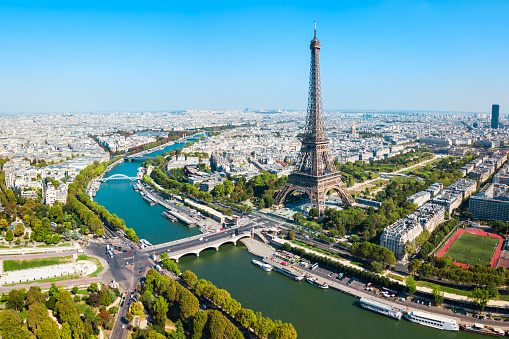 An aerial view of the city of Paris, looking at the Eiffel Tower on a sunny day.
