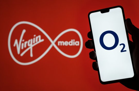 Stone / UK - May 12 2020: O2 Telefonica logo on smartphone screen hold in hand and Virgin Media logo on blurred background. Concept for Virgin and O2 merger.; Shutterstock ID 1729743754; Purchase Order: -
