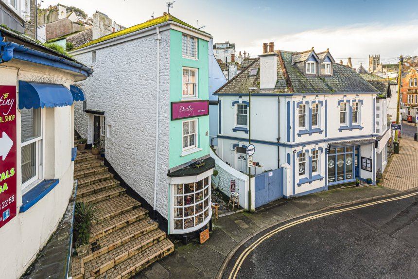 These pictures show one of Britain's most unique homes - known as the Coffin House it is a Grade II listed building close to the harbour in Brixham, Devon, and dates back to 1736. See SWNS story SWPLcoffin. These pictures show one of Britain's most unique homes - the only one in the world shaped like a COFFIN. The property - known as the Coffin House - is a Grade II listed building close to a harbour and dates back to 1736. Formerly known as Ye Olde Coffin House, the building in Brixham, Devon, is understood to have been built due to a row between a daughter and her father over a man he didn't want her to marry. The dad reportedly told his future son-in-law: