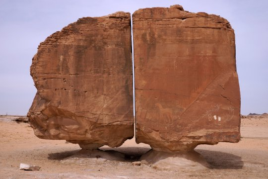 Amazing natural split rock with each half perched on small stone plinths, Taymah Oasis; Shutterstock ID 1670198365; purchase_order: -; job: -; client: -; other: -