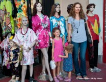mom and girls pose along side manequins clad in Chinese silk robes