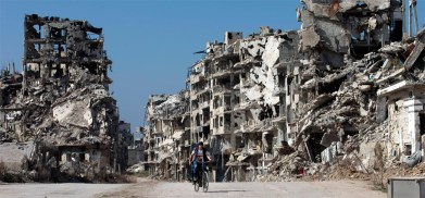 joven-pasa-bicicleta-ayer-entre-los-edificios-destruidos-ciudad-vieja-homs-siria-1457619410864