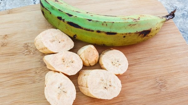 Green plantains cut into one inch slices on cutting board ready to pre-fry-Fried Plantains Recipe