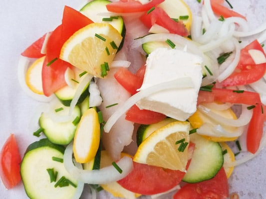 Tilapia fillets with zucchini, yellow squash, tomatoes, onions, garlic, lemon wedges and butter prepared on top of parchment paper-Tilapia en Papillote Packets (Tilapia in Parchment Packets).
