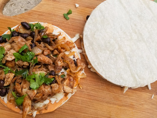 Assembly of the Smoky Black Bean Chicken Quesadillas on a wooden cutting board.