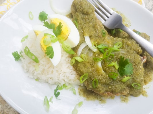 Chuletas de Puerco or Chuletas de Puerco en Salsa Verde (Pork Chops in Salsa Verde served with white rice, thin slices of onions and a quartered hard boiled egg sitting on top and served on a white plate.