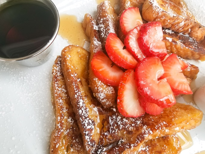 Dulce de Leche French Toast served with a side of Cinnamon Sauce and topped with confectioners sugar, syrup and sliced strawberries served on a white plate.