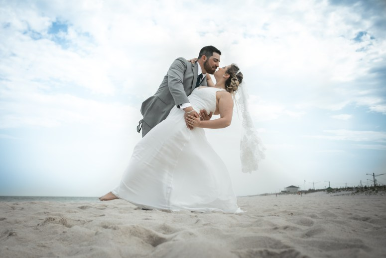 newlyweds kissing at beach
