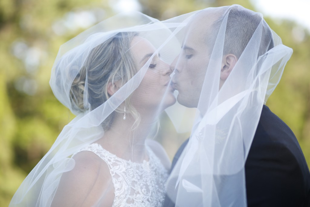 couple kissing under wedding veil