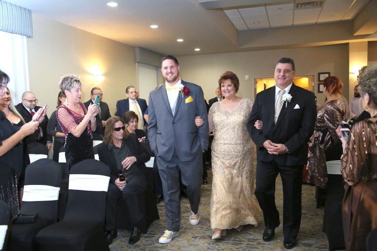 the groom walking with his parents
