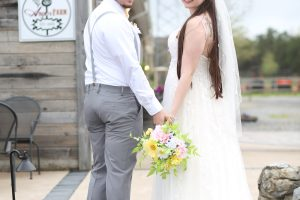 bride and groom holding hands at farm in NJ