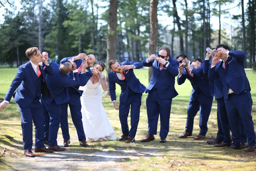 bride and groom with groomsmen shotgunning beer at wedding in 2019