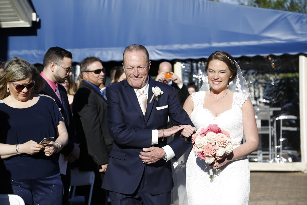 bride walking down the aisle with her father at wedding in 2019