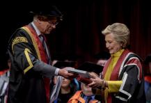 US politician Hillary Clinton, right, receives a Honorary Doctorate and is also handed a book of her Welsh family history by Pro-Chancellor Roderick Evans, at Swansea University, in recognition of her commitment to promoting the rights of families and children around the world, in Swansea, Wales, Saturday, Oct. 14, 2017. (Ben Birchall/PA via AP)