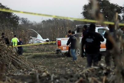 Police and rescue personnel stand at the scene where the helicopter transporting Martha Erika Alonso, governor of the state of Puebla, and his husband Senator Rafel Moreno Valle crashed, in Coronango, Puebla Mexico, December 24, 2018. REUTERS/Imelda Medina