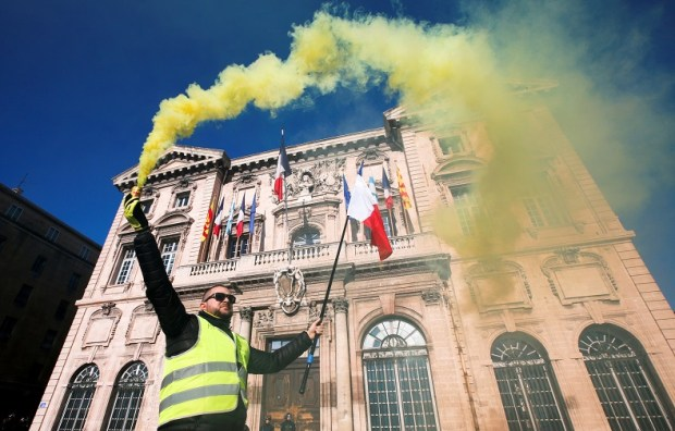 """A protester wearing yellow vest holds a flare in front of the town hall as he takes part in a demonstration of the """"yellow vests"""" movement in Marseille"""