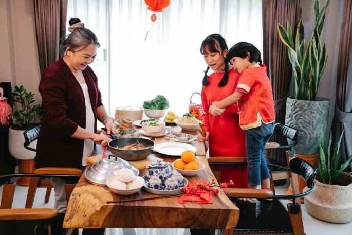 positive asian woman cooking chinese food for festive occasion