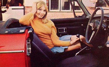 Beautiful women sitting in the passenger seat of a MGB