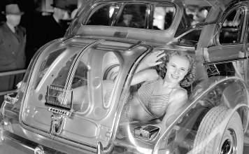 Gal in the trunk of a clear Pontiac