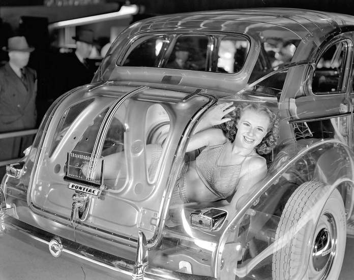 Gal in the trunk of a clear Pontiac