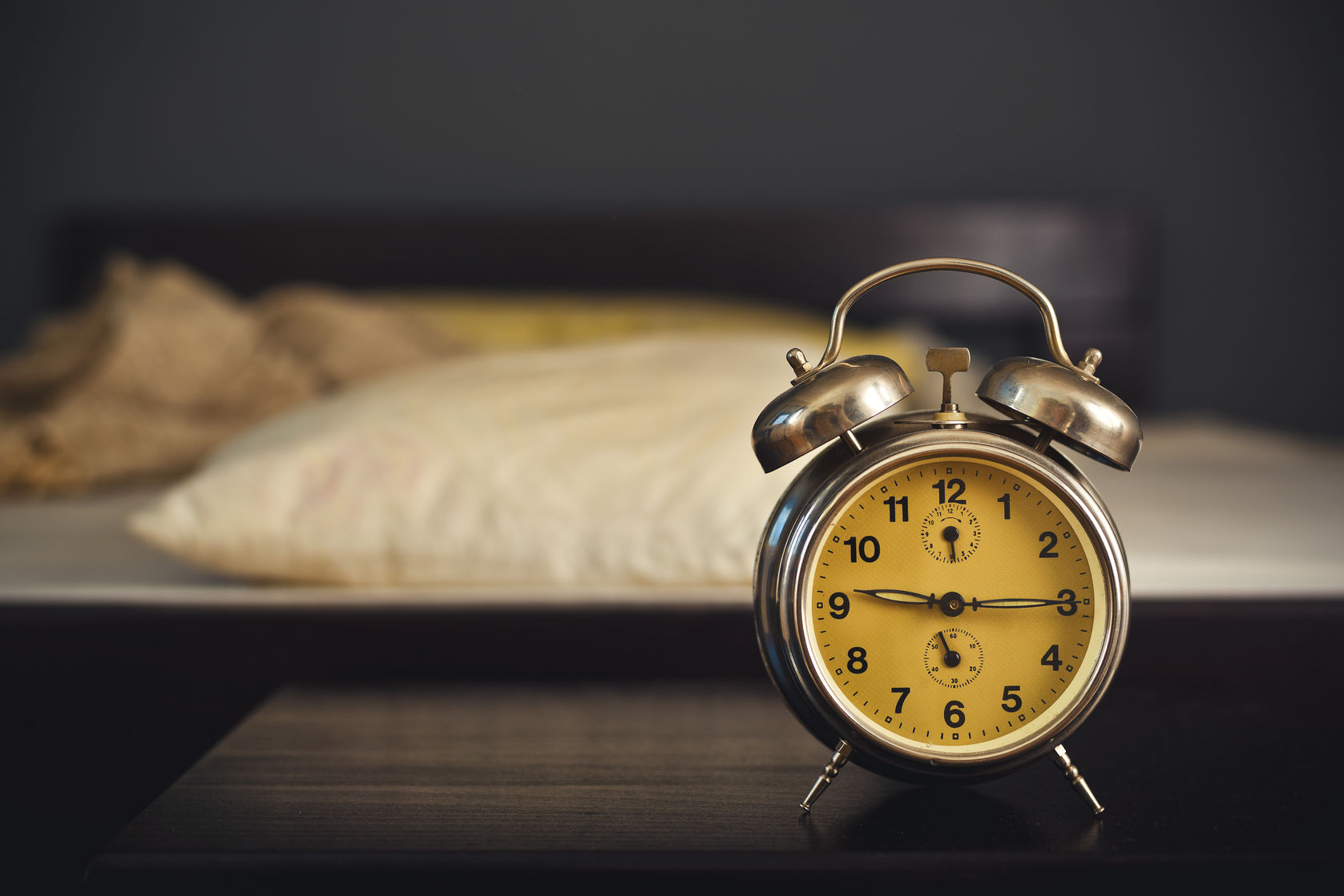 25824695 - vintage alarm clock in bedroom on a night table by the bed