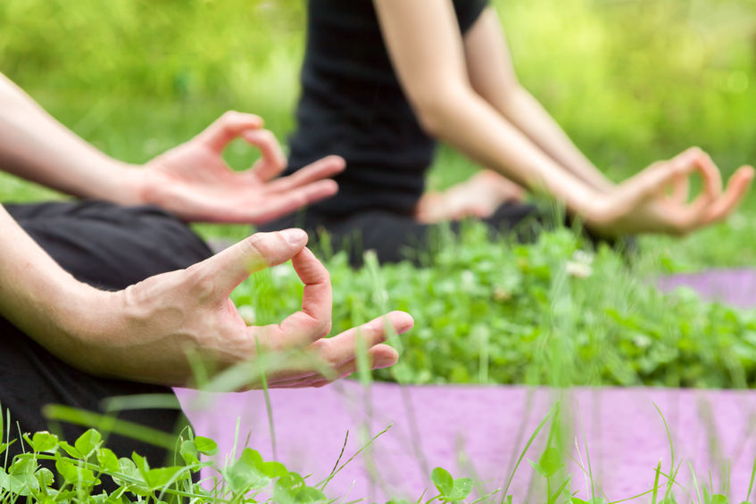 31225312 - man and woman doing yoga in lotus position sitting on grass