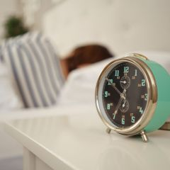 54149287 - alarm clock about to ring alongside a sleeping person in bed with focus to the bedside table ad clock
