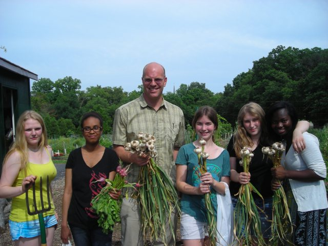 Members of the T.C. Williams Garden club harvested radishes and garlic in May 2012. Faculty advisor and Master Gardener Patrick Earle is at center; club President Katja Shimkin is at left.