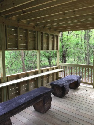 A bird blind, laminated maps, and educational signage provide help visitors understand the role of wildlife in the forest habitat.