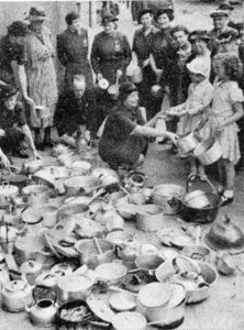 Lord Beaverbrook's appeal to housewives for aluminium goods brought an immediate and overwhelming response. Lady Lucas Tooth, in charge of the W.V.S. at Chelsea, is here seen receiving contributions at the Town Hall.