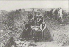 Gravediggers struggle to hew a trench from a rocky field