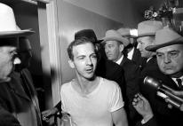 Surrounded by detectives, Lee Harvey Oswald talks to the press as he is led down a corridor of the Dallas police station for another round of questioning