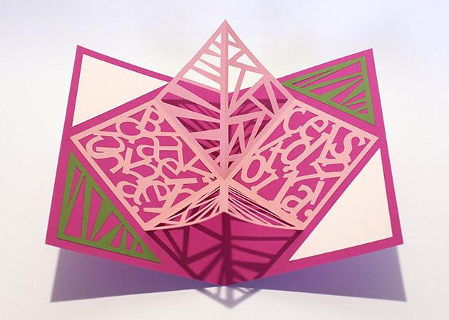 Carré plié d'anniversaire personnalisé avec motifs triangles sur fond fuschia. Carte vue de dessus