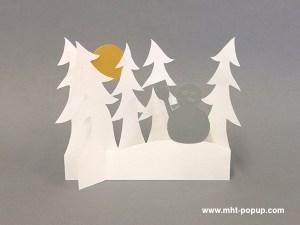 Décoration de Noël en papier découpé avec forêt de sapins et bonhomme de neige. Papier blanc, or, argent et cuivre. Pliage pour créer une scène en volume