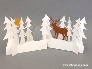 Décorations de Noël en papier découpé avec forêt de sapins, cerf et bonhomme de neige. Papier blanc, or, argent et cuivre. Pliage pour créer une scène en volume