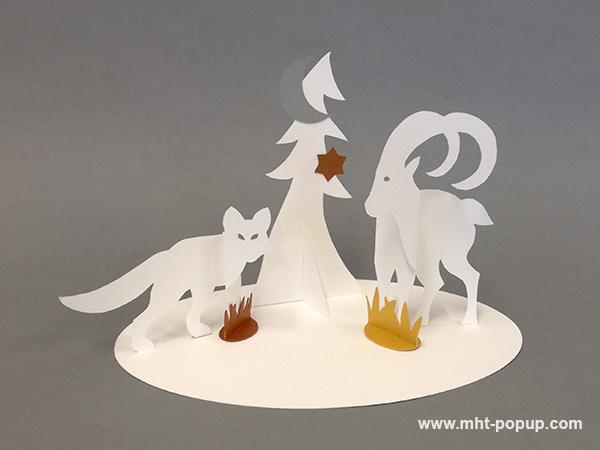 Saynète animalière d'hiver en papier découpé, modèle renard, bouquetin et sapin. Papier blanc, or, argent et cuivre.