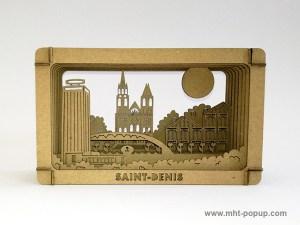Diorama en carton brut avec éléments du patrimoine de Saint-Denis (Basilique, canal, marché, tour Pleyel…), à monter soi-même. Vue de face